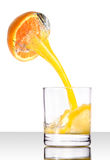 Orange juice pouring from fruit in a glass Stock Photo