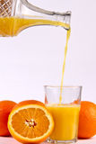 Orange juice pouring into glass. Stock Image