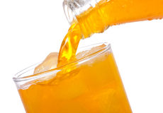 Orange juice is pouring into glass Stock Image