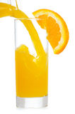 Orange juice is pouring into glass Royalty Free Stock Image
