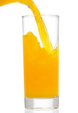 Orange juice is pouring into glass Royalty Free Stock Photos