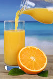 Orange juice pouring into glass on the beach Stock Images