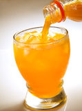 Orange juice pouring into glass Stock Image