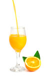 Orange juice pouring into glass with orange slice and leaf Stock Photos