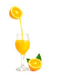 Orange juice pouring into glass with orange slice and leaf Royalty Free Stock Image
