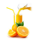 Orange juice pouring into a glass and oranges Royalty Free Stock Image