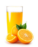 Orange juice pouring into glass and oranges with leaves Royalty Free Stock Image