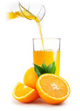 Orange juice pouring into glass and oranges Royalty Free Stock Photo