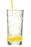 Orange juice pouring into glass on white background Royalty Free Stock Images