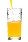 Orange juice pouring into glass on white background Royalty Free Stock Photo