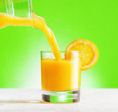 Orange juice pouring from jug into a glass Stock Photography