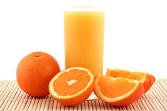 Orange juice and ripe oranges. Fresh orange juice and juicy orange on bamboo matting royalty free stock photography