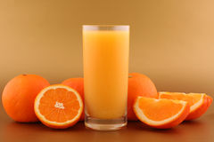 Orange juice and ripe oranges. Orange juice, fresh ripe orange and orange slices on gold background Stock Photos