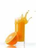 Orange juice splash. In glass with fruit on side Stock Photo