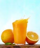 Orange juice splash. And fresh oranges Royalty Free Stock Photography