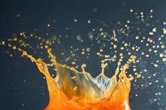 Orange juice splash over dark background Royalty Free Stock Photos