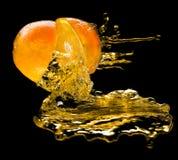 Orange and juice splashes. On a black background Stock Images
