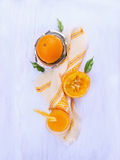 Orange juice, Squeezed fruit and stainless steel citrus juicer on blue woden. Background, top view Stock Image