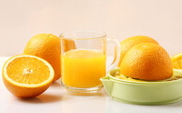 Orange juice squeezer. Oranges, a glass of juice and juice extractor on the kitchen table Stock Photos