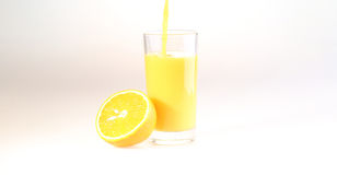 Orange juice a stream flows in a transparent glass,a glass with. Orange juice a stream flows in a transparent glass, a glass with orange juice on a white stock image