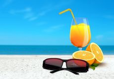 Orange Juice and Sunglasses at the Beach Royalty Free Stock Image
