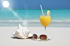 Orange juice and sunglasses on the beach Royalty Free Stock Images