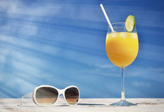 Orange juice and sunglasses Stock Photos