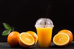 Orange juice in takeaway plastic cup with fresh fruits. On dark table stock photo