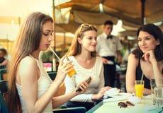 Orange juice. Three friends drinking orange juice at a cafe Stock Photography