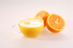 Orange juice in a transparent cup and halves of a juicy ripe ora. Nge on a white background royalty free stock photography