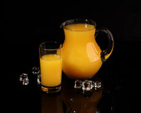 Orange juice in a transparent jug on a black background. Orange juice with ice stock photo
