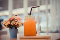 Orange juice with a vase of flowers. Royalty Free Stock Photo