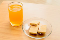 Orange juice and Wafer on the wooden table Stock Image