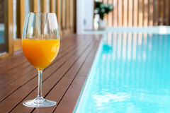 orange juice in wine glass on edge  the blue sky pool Stock Images