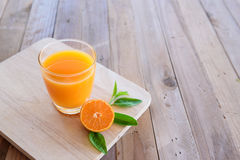 Orange juice on wooden background stock photos