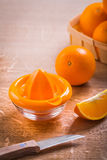Orange juicer and fruits with kitchen knife on Stock Photography