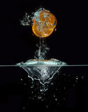 Orange jumping out of the water. Orange slice jumping out of the water, isolated on black Stock Image