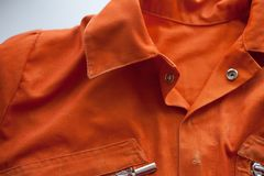 An orange jumpsuit of a prisoner. Serving of compulsory execution of court decisions. An orange jumpsuit of a prisoner. close up. Serving of compulsory execution stock photo