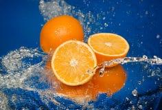 Orange juteuse dans le jet de l'eau images stock