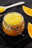 Orange Körperpeeling mit Zucker und Kokosnussöl im Glasgefäß auf Weinlesehintergrund Selbst gemachte Kosmetik für die Schale und  Lizenzfreies Stockfoto