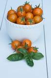 Orange körsbärsröda tomater i en vit bunke Arkivfoto