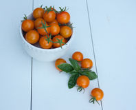 Orange körsbärsröda tomater i en vit bunke Arkivbilder