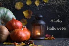 Orange Kürbise Halloween-Konzeptes, eine Laterne mit Kerzen und Laub auf einem dunklen Hintergrund mit einem Spinnennetz stockfotografie