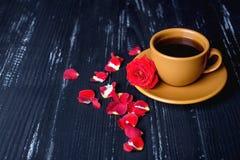 Orange Kaffeetasse mit den rosafarbenen Blumenblättern auf dem schwarzen Hintergrund Stockfotos
