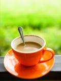Orange kaffekopp med naturbokeh Arkivbilder
