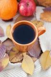 Orange kaffekopp på höstnedgångsidorna Royaltyfri Bild