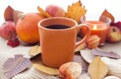 Orange kaffekopp på höstnedgångsidorna Arkivfoton