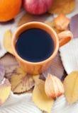 Orange kaffekopp på höstnedgångsidorna Arkivbild