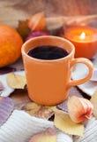 Orange kaffekopp på höstnedgångsidorna Royaltyfri Foto