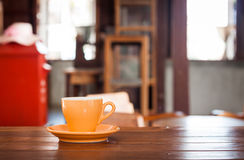 Orange kaffekopp på trätabellen Royaltyfria Bilder